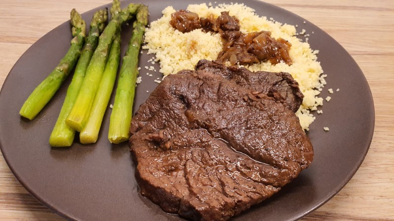 Dutch oven braised sliced beef with couscous and asparagus