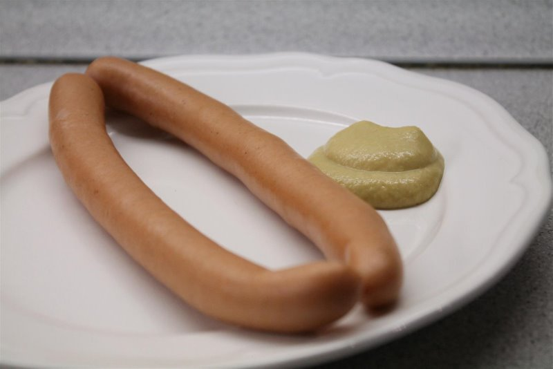 Boiled hot dogs with mustard on a plate