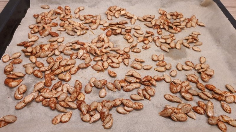 Pumpkin seeds with spices on a baking tray